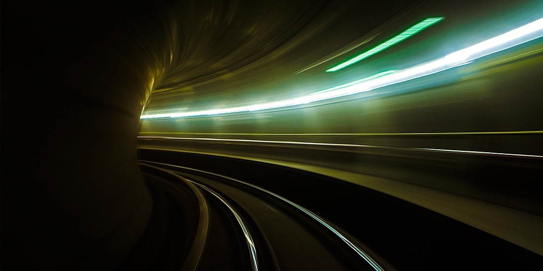 Long exposure image of a rail track with light traces at the side
