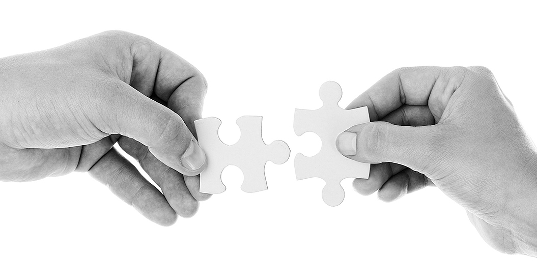 Two people putting together 2 separate pieces of Jigsaw