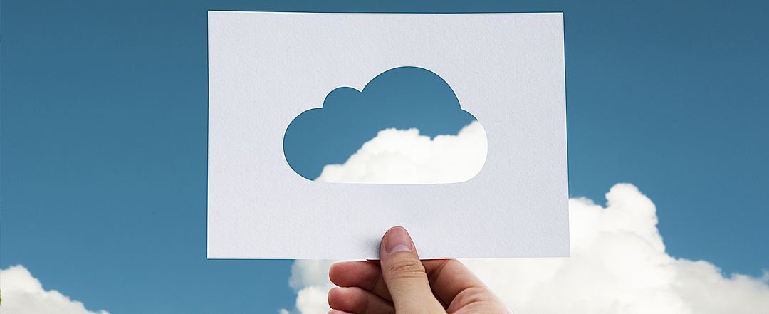 Person holding piece of paper with a cloud cut out and sky behind