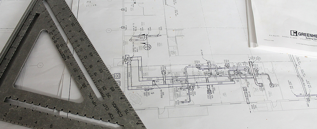 Close up of engineering drawing and set square on table