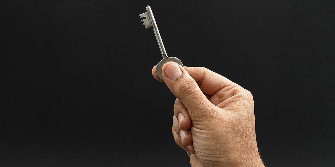 Close up on man holding a key in the air