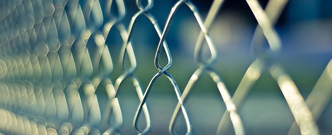 Close up on chain link fence with a blue background